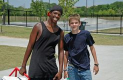Best Buddies. Two teenaged boys shown hanging out together at the skatepark Royalty Free Stock Photo