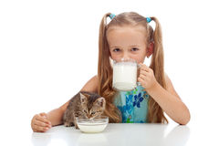 Best buddies drinking milk together. Little girl and her kitten Royalty Free Stock Photo
