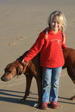 Best buds. A beautiful white caucasian girl child holding her ridgeback dog on the beach Stock Images