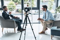 Best business vlog. Two young men in smart casual wear talking while making new video indoors stock image