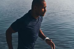 Best cardio ever. Young African man in sports clothing jogging while exercising near the river outdoors stock image