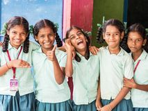 Best children friends girls classmates smiling laughing standing with hand on shoulder at the school. Multiethnic school kids stock image