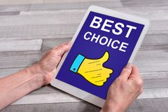Best choice concept on a tablet. Female hands holding a tablet with best choice concept Stock Image