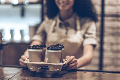 Best coffee to go!. Part of young cheerful African woman in apron holding coffee cups while standing at cafe Royalty Free Stock Image