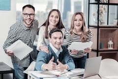 Pleasant happy employees standing near the table and smiling. The best company. Pleasant happy enjoyed employees standing in the office near the table smiling royalty free stock image