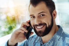 Stylish joyful man having phone conversation and smiling. Best connection. Stylish beardful joyful man having phone conversation smiling and looking straight Stock Photo