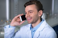 Young satisfied expert smiling and having phone conversation. stock photography