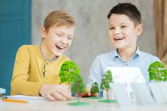 Joyful boys having fun while working on ecology project. Best cooperation. Cheerful pre-teen boys sitting at the table full of models and laughing while working royalty free stock photos