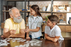 Grandfather and grandchildren assembling jigsaw puzzle altogether Royalty Free Stock Image
