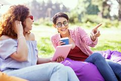 Inspired girl relaxing with her friend. Best day. Cheerful curly-haired women holding a tablet and talking with her friend Royalty Free Stock Photo