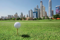 The best day for golfing. Golf ball is on the tee for a golf bal. L on the grass on a golf course on the background of the city skyscrapers Royalty Free Stock Image