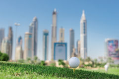The best day for golfing. Golf ball is on the tee for a golf bal. L on the grass on a golf course on the background of the city skyscrapers Stock Image