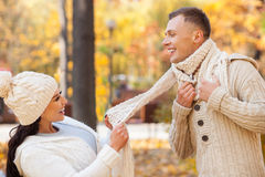 This is the best day in my life. Attractive young loving couple is making fun in the autumn park. They are standing and laughing. The women is holding the scarf stock images