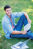 Best day at the university. Cute male student holding a book and. Looking at the camera while sitting on the grass near the campus of the University at the Royalty Free Stock Photos