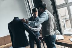 Best designs. Two young fashionable men measuring jacket?s sleeve while standing in workshop stock photography
