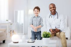 Cheerful male doctor completing boys examination. Best doc. Afro American positive male doctor wearing uniform while grinning and boy standing next to him Royalty Free Stock Photos
