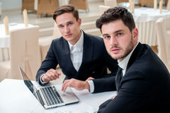 The best employees. Two successful and confident businessman sit. Ting at the table in a business office in full costume in the office and working at a laptop Stock Photos