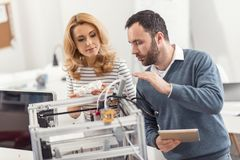 Bristled engineer explaining how to use 3D printer. Best explanation. Charming bristled engineer explaining to his female colleague how to use a 3D printer while stock images
