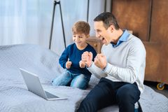 Overjoyed father and son watching football game online Stock Photo
