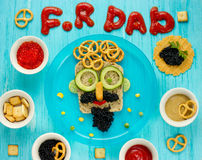 Best Father`s Day brunch idea - funny face sandwich with black c. Aviar and vegetables on table with snacks Stock Images