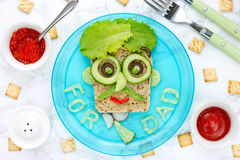 Best Father`s Day brunch idea - vegetables cheese funny sandwich. Shaped man face Stock Photo