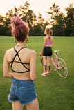 Best female friends with bicycle having fun royalty free stock images
