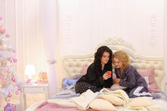Best female friends watch news on Internet on smartphone and cha Royalty Free Stock Photo