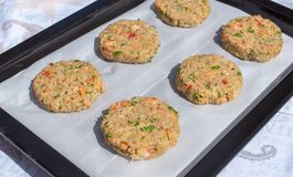 Best fish cakes raw uncooked on  baking tray. .Row of crab patties.  stock photography