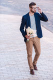 The best flowers for her. Full length of handsome young man in smart casual wear holding bouquet of flowers and adjusting his eyeglasses while walking by the Stock Images