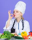 The best foods for every vitamin and mineral. Professional cook gesturing ok. Pretty woman chef with vitamin vegetables stock photography