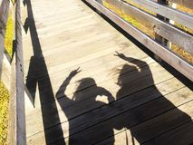 Best friend concept picture, black shadow of two people showing peace hand sign on wooden path way Royalty Free Stock Photography