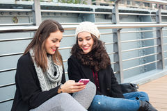 Best friend girls with mobile Royalty Free Stock Photography