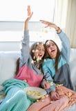 Best friend girls at sofa having fun with popcorn stock photo