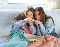 Best friend girls at sofa having fun with popcorn stock photos