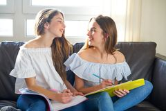 Best friend girls studying homework at home. In sofa Stock Photo