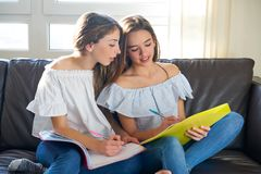 Best friend girls studying homework at home. In sofa Stock Photography