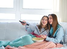 Best friend girls watching TV cinema best friend girls watching. Best friend girls watching TV cinema at home with popcorn Royalty Free Stock Images