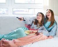 Best friend girls watching TV cinema best friend girls watching. Best friend girls watching TV cinema at home with popcorn Stock Image