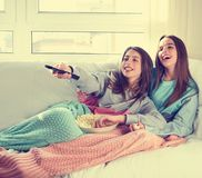 Best friend girls watching TV cinema best friend girls watching. Best friend girls watching TV cinema at home with popcorn Stock Photography