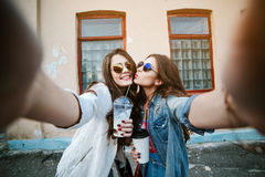 Best friend having fun on the roof, freaking out together, wearing bright floral shirts, denim jackets and mirrored. Glasses show a sign of peace, enjoy Stock Images