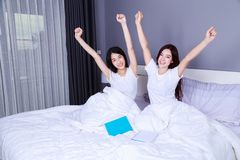 Best friend woman with arms raised on bed in bedroom Stock Photography