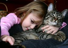 Best Friends. Adorable little girl snuggling with her pet cat royalty free stock photo
