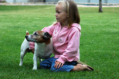 Best friends. A beautiful caucasian blond little girl and her Jack Russel Terrier dog pet on the lawn in the garden outdoors Stock Photos