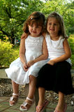 Best Friends. Two girls sitting together outside on a bench stock photography