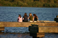 Best friends. Four girls spending the late afternoon on the docks sharing stories and having fun Royalty Free Stock Photography