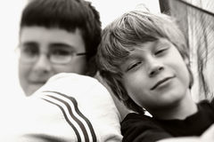 Best friends. Black and white picture of two smiling boys. because of the use of a special focus adjustment, focus is narrow and just down the middle of the Royalty Free Stock Image