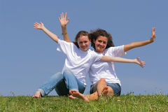 Best friends. Two teen girls wave hands against a blue sky Stock Images