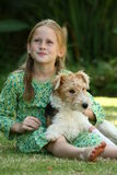Best Friends. A white Caucasian girl sitting on the grass with her puppy Stock Photo