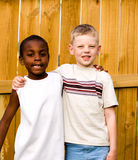 Best friends. Two boys stand outside with arms around each other Stock Photo