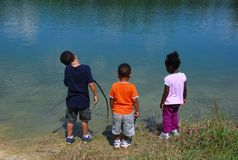 Best Friends. Three young children enjoying a summer day together fishing at a local lake Stock Photos